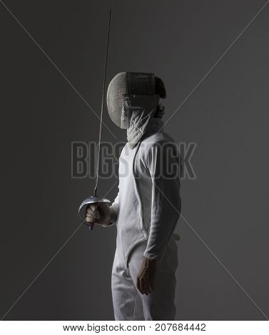Portrait of a fencer in fencing mask with the sword on grey background