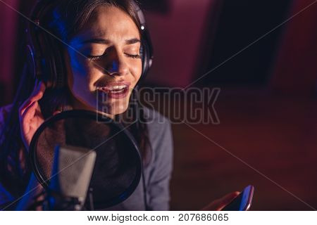 Female Singer Recording A Song In Studio