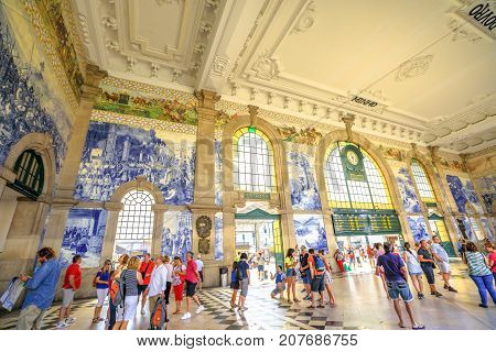 Porto, Portugal - August 13, 2017: people on interior of historic station of Porto. Azulejos, painted ceramic tileworks on the walls of main hall of Sao Bento Railway Station, a Unesco Heritage Site.
