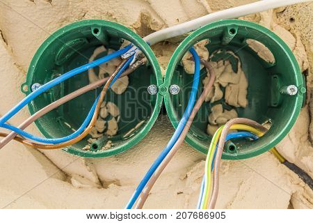 New electrical installation socket plastic boxes and electrical cables on the wall renovation concept. Electrical wiring installation.