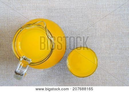 Jug and glass of orange juice from above top view on burlap sackcloth background