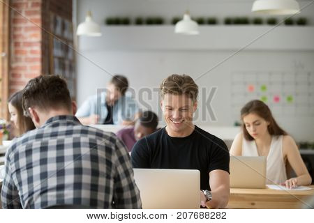 Smiling casually dressed businessman looks at laptop screen at work in shared office. Young entrepreneur enjoying good day at work, reading optimistic corporate news, success in stock market concept.
