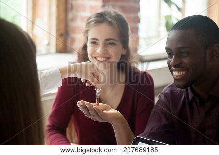 Real estate agent handing new house keys to happy multiethnic couple. African american man and his wife are excited to buy new house or apartment. Young interracial couple bought first home together.