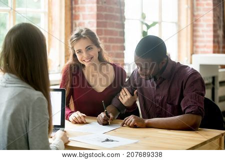 African american man signing home purchase agreement in front of realtor, his smiling wife sitting near and looking at female real estate agent. Young multiethnic family leasing new apartment concept.