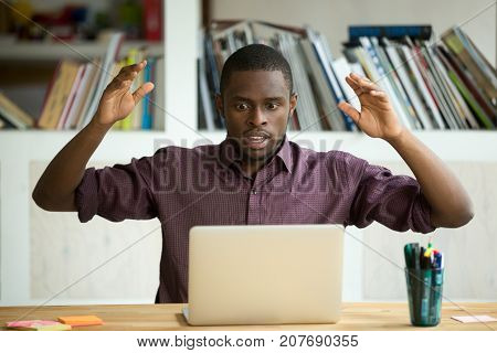 Shocked young african american office worker looking at laptop screen throwing arms in the air. Horrified small business owner sees app error, lost documents because of unexpected bad computer crash.