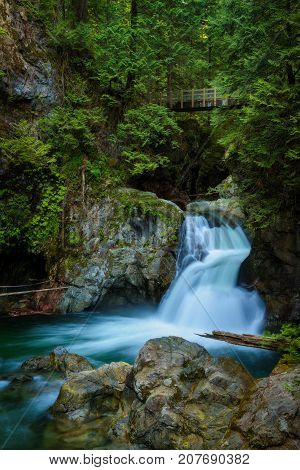 Twin Falls in Lynn Canyon Park with footbridge, North Vancouver, Canada. Long exposure.
