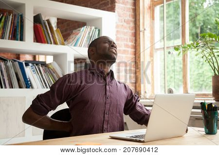 Young exhausted african american male office worker having back discomfort at work desk in office. Fatigued casual businessman feeling back pain after sitting on uncomfortable chair for long hours.