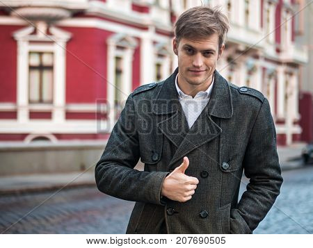 Businessman hand showing OK sign, autumn street background. Portrait of young successful confident businessman in the city. Man in a business suit.