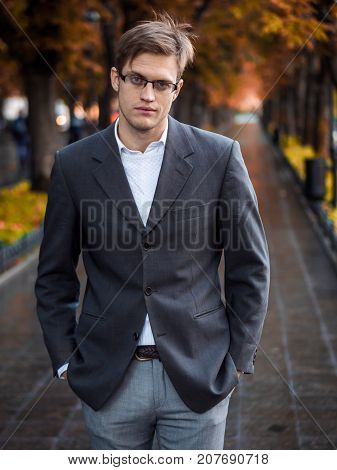 Portrait of young successful confident businessman in the city. Man in a business suit and glasses in the autumn street. Portrait of handsome guy.