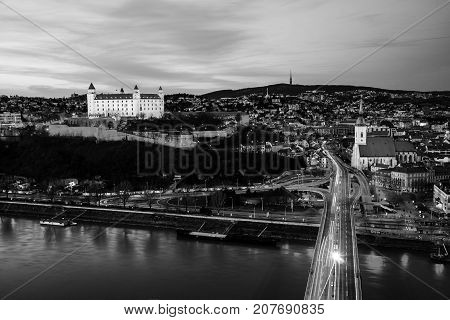 Bratislava, Slovakia. Aerial view of the castle and illuminated historical buildings with car traffic and river in the capital of Slovakia Bratislava. Black and white