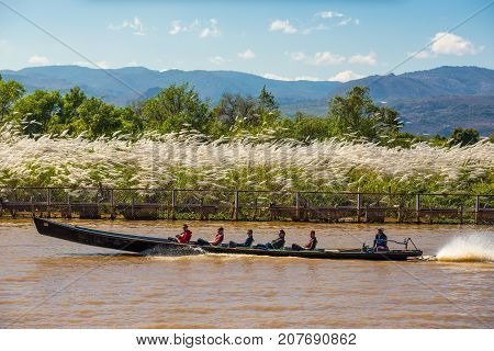 AVA, MYANMAR - JANUARY 27, 2016 : Tourists travel in a  long-tail boat through local villages in Myanmar