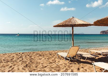 Beach sunbed and parasol overlooking turquoise water