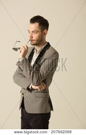 stylish man with an unshaven face with a pensive face, in a suit on a light background