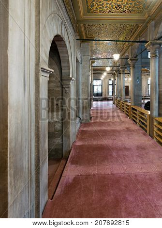 Istanbul Turkey - April 24 2017: Passage in Eyup Sultan Mosque with marble wall decorated painted ceiling and red carpet