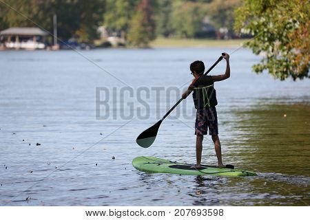 Silhouette of stand up young boy paddle boarder paddling on a flat warm quiet lake