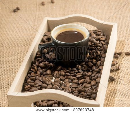 Coffee grains in wooden box and black cup of coffee. Coffee cup. Strong coffee. Coffee mug. Morning coffee. Coffee break