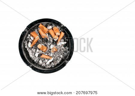 Dirty black ceramic ashtray with a cigarette full of smoked butts view from above