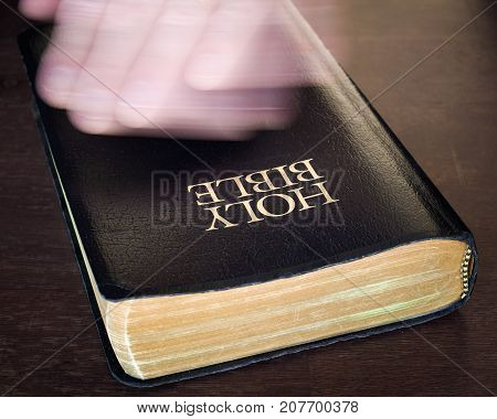 Hand in spiritual motion over Holy Bible.