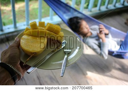 Dad feed a mango to his daughter who's only interested with the phone.
