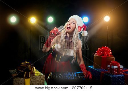 DJ girl in santa hat sings into microphone on Christmas day.  DJ's in the New Year.