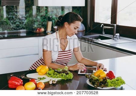 Young Happy Woman In Apron Looking At Recipe In Tablet In The Kitchen. Vegetable Salad. Diet. Dietin