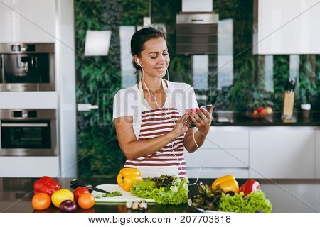 Young Happy Woman With Headphones In The Ears Holding Mobile Phone In Hands In Kitchen. Vegetable Sa