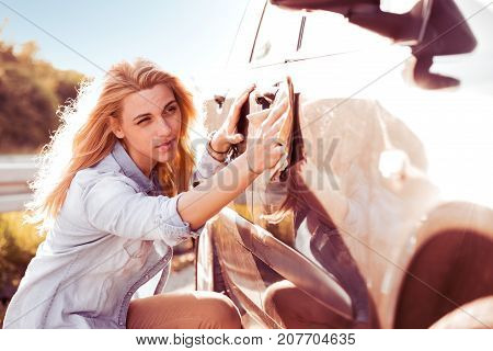 Young woman cleaning car with microfiber cloth car detailing .