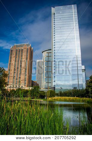 Vertical Modern Silver Tower Skyscraper at the Discovery Green Park with fresh friendly inviting pond in downtown Houston , Texas , USA