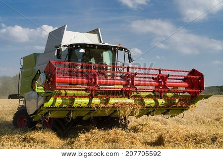 green red working harvesting combine in the field of wheat in front of a blue cloudy sky front view