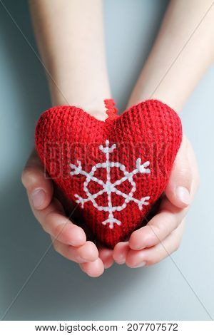 Christmas  knitted heart in child hands closeup