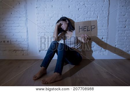 lonely young attractive Hispanic woman sitting at home floor frustrated suffering depression feeling sad and desperate with a headache in problems and broken heart concept asking for help