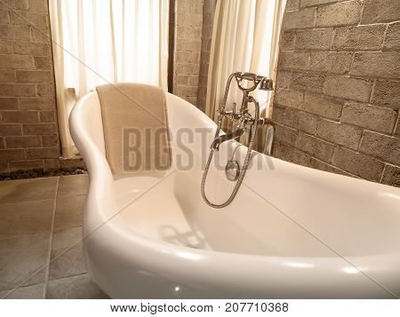 Vintage tone of brown towel on white bathtub in bathroom at the modern hotel (Selective Focus)