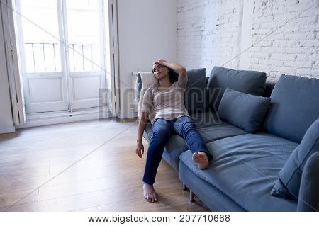 young attractive latin woman lying at home living room couch tired and worried suffering depression feeling sad and desperate with a headache in problems and broken heart concept