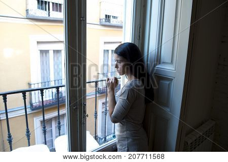 young attractive latin woman lying at home looking through window frustrated suffering depression feeling sad and desperate with a headache in problems and broken heart concept