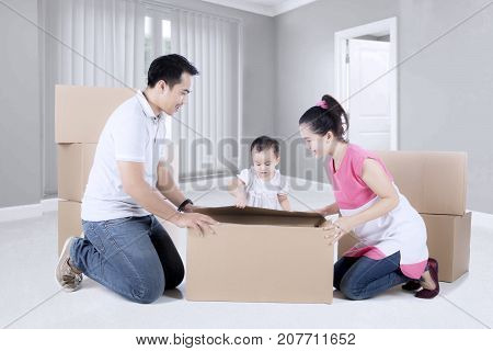 Picture of a young family unpacking cardboard while sitting with a pile of cardboard in the new home