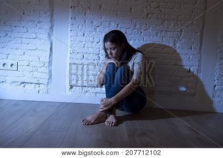 lonely young attractive Hispanic woman sitting at home floor frustrated suffering depression feeling sad and desperate with a headache in problems and broken heart concept