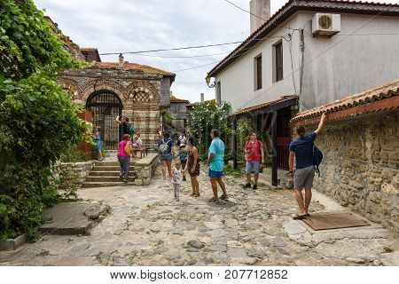 NESEBAR BULGARIA - AUGUST 21 2017: A street with tourists in the old town and in the background of the Church of the Holy Archangels Michael and Gabriel (built between the 13th and 14th centuries).