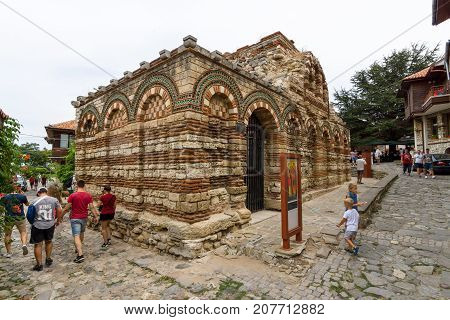 NESEBAR BULGARIA - AUGUST 21 2017: Church of the Holy Archangels Michael and Gabriel (built between the 13th and 14th centuries) and a street with tourists in the old town.