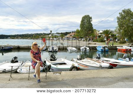 Ipsos Corfu Greece - September 29 2017 : Lady taking a selfie at Ipsos Marina in Corfu
