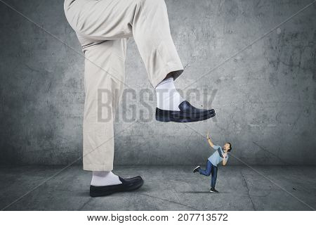 Picture of scared African man wearing sportswear while running from his boss foot