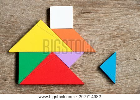 Colorful tangram puzzle in home shape wait for fulfill on wood background (Concept for build dream house happy family life property investment)