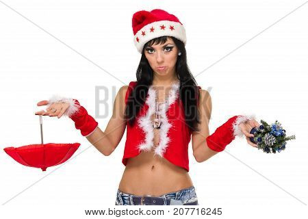 girl wearing santa claus clothes with an umbrella and small Christmas tree posing against isolated white background