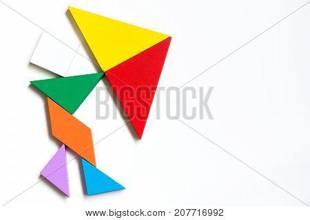 Colorwood tangram puzzle on human hold the umbrella shape on white background