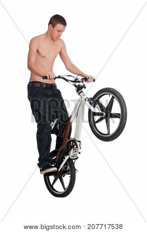 Teenage boy standing on the rear pegs of a BMX bike while performing stunts.