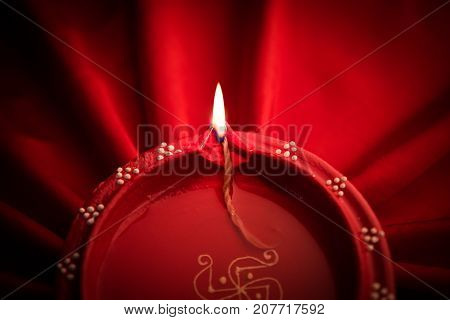Big illuminated diwali diya or clay lamp placed over satin cloth creating rays effect in cloth, moody lighting, selective focus