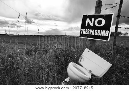 A black and white image of a no trespassing sign and white porcelain toilet in a field.
