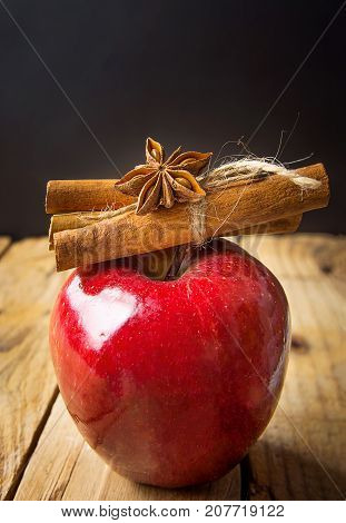 Red Glossy Apple Cinnamon Sticks Tied with Twine Anise Star on Wood Background. Vintage Rustic Style. Christmas New Year Symbol. Greeting Card Poster Template. Copy Space