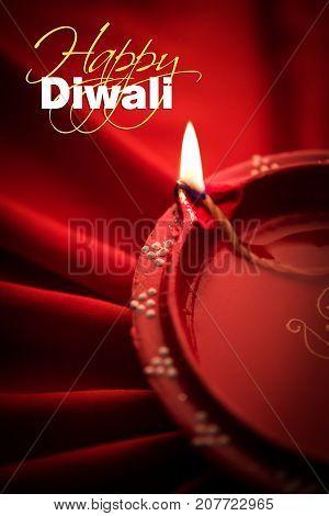 Happy diwali greeting card - Big illuminated diwali diya or clay lamp placed over satin cloth creating rays effect in cloth, moody lighting, selective focus