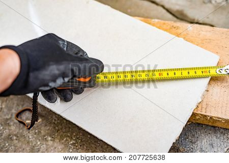 The Process Of Measuring The Length Of A Sheet Of Drywall