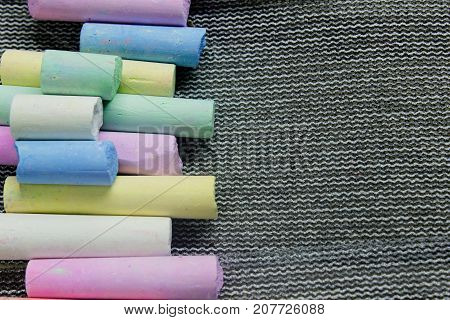 multi-colored chalk on a gray background close-up. view from above